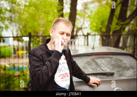 Portrait of a man with a beard with a mustache, smoking a cigarette, with an emotional face in the open air - Stock Photo