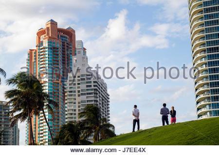 Miami Beach Florida South Pointe Park man woman couple high-rise condominium buildings palm trees - Stock Photo