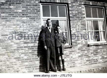 young adult man and boy posing early 1950s Netherlands - Stock Photo