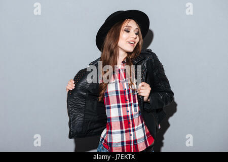 Picture of smiling young lady standing over grey background. Looking aside. - Stock Photo
