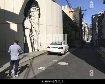 Tokyo, Japan. 23rd May, 2017. A mural of a girl with the face cover can be seen in the streets of Tokyo Japan on - Stock Photo