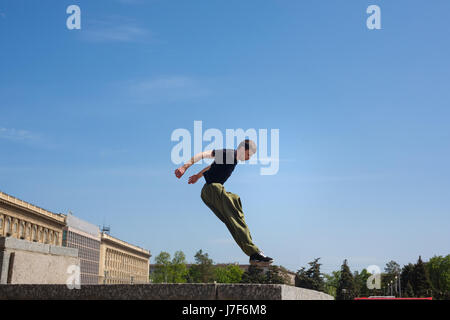 Young man jumps on the wall. Parkour in the urban space. Sports in the city. Sport activity. - Stock Photo