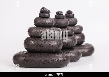 Wet smooth polished hot massage black stones covered with water drops - Stock Photo