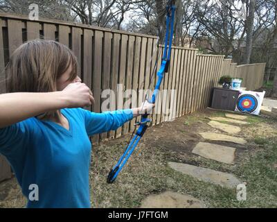 Young Girl Shooting Bow and Arrow - Stock Photo