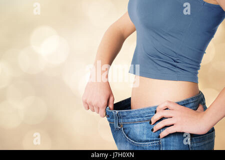 Thin woman in big pants - weight loss concepts - Stock Photo