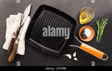 Black iron empty grill pan, seasonings and meat fork on stone texture background - Stock Photo