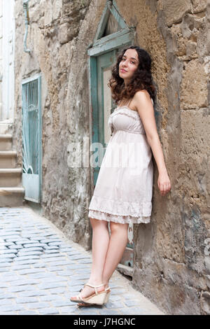 Young girl near old wall in downtown in Baku - Stock Photo