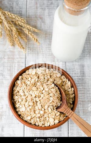 Organic oat flakes, rolled oats in brown ceramic bowl, wheat ears and bottle of milk on rustic white table. Vertical - Stock Photo