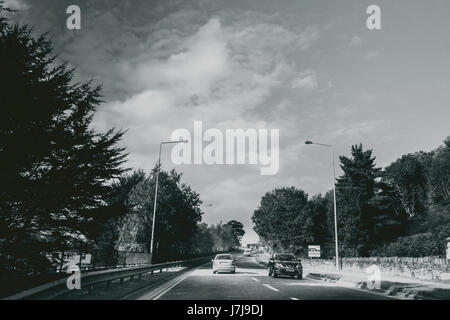 Shot of the highway leading towards the killarney national park with a dramtic sky in the depth. - Stock Photo