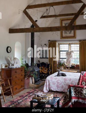 Bright kelim in airy bedroom with ceilings beams, woodburning stove and Sophie ryder sculptures - Stock Photo