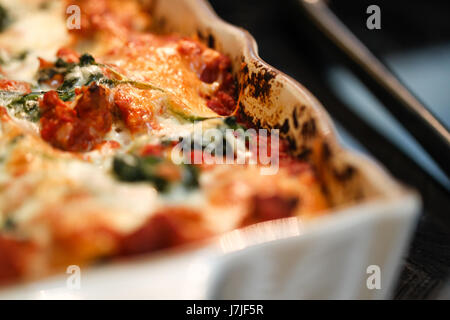 Closeup. Out of the oven-fresh, baked cheese lasagna, shown here in a white enameled baking dish. - Stock Photo