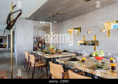 Laura Meroni brass hanging lights above custom made stonewood marble dining tables with photographic work by Alex - Stock Photo