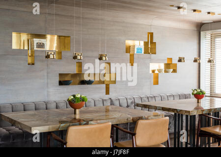 Laura Meroni brass hanging lights above custom made stonewood marble dining tables with grey velvet buttoned banquette - Stock Photo