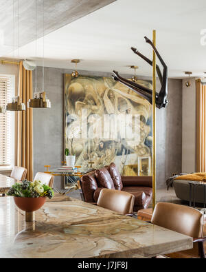 Laura Meroni brass hanging lights above custom made stonewood marble dining tables - Stock Photo