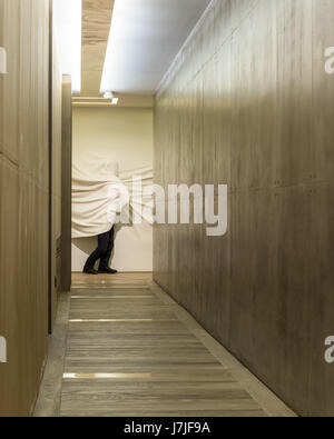 Shrouded figure sculpted from powdered glass by Daniel Arsham in hallway with polished concerete walls - Stock Photo