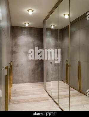 Mirrored wardrobes in dressing room with polished concrete walls - Stock Photo