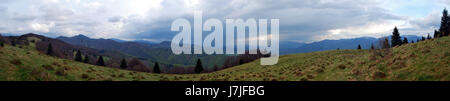 spectacular mountain panorama of Velka Fatra and Mala Fatra mountain ranges with many hills and meadows from Nolcovska - Stock Photo