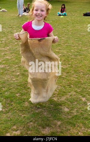 Seven-year-old girl / Child / kid takes part in summer sack race. UK (87) - Stock Photo