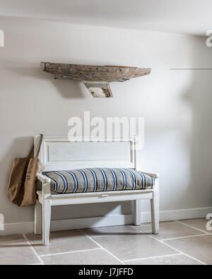 A driftwood boat on wall above antique bench with ticking stripe cushion. The walls are painted in Farrow & Ball - Stock Photo