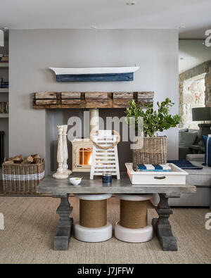 A pair of capstan stools under thick-set wooden coffee table in sitting room with jotul wood stove. the walls are - Stock Photo