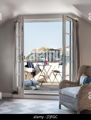 View through open doors to decked balcony with harbor view. The rattan armchair is from The Country Home - Stock Photo