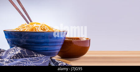 cooked Japanese wheat noodles in a blue ceramic bowl with wooden chopsticks on wooden table, room for copy space - Stock Photo