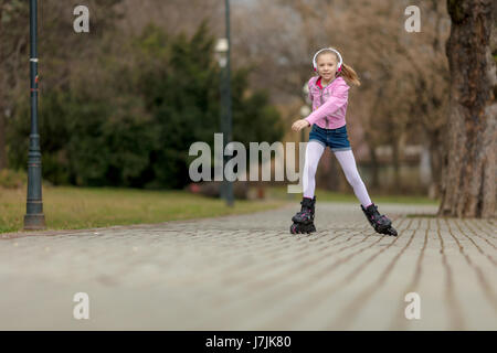 Beautiful smiling little girl inline skating through the park. - Stock Photo