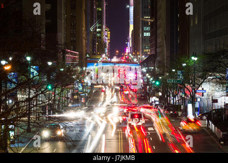 Night Time Long Exposure View Down 42nd Street To Pershing Square With Busy Traffic On Road, New York - Stock Photo