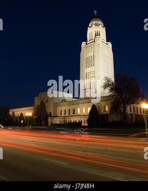 Cars Sreak By at Night in front of Lincoln Nebraska State Capital Building - Stock Photo