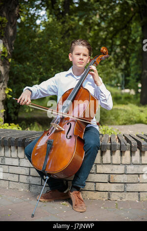 Boy playes on the contrabass in the park - Stock Photo
