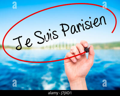 Man Hand writing Je Suis Parisien with black marker on visual screen. Isolated on nature. Stock Photo - Stock Photo