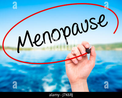 Man Hand writing Menopause with black marker on visual screen. Isolated on background. Business, technology, internet - Stock Photo