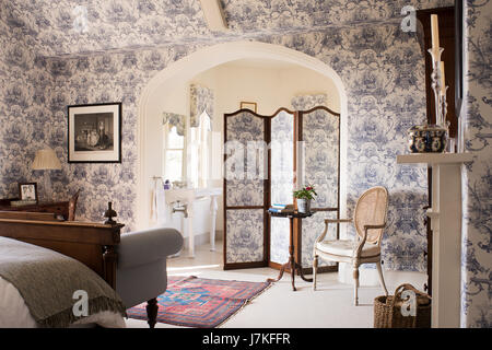 Large ensuite bedroom with toile de jouy wallpaper and matching folding screen. - Stock Photo