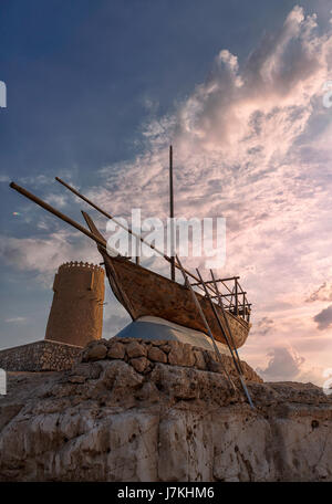 Monument of Dhow boat next to tower along the Al Khor corniche in Qatar, Middle East. - Stock Photo