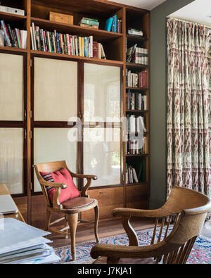 A pair of wooden chairs sourced by Retrouvius in study with patterned rug - Stock Photo
