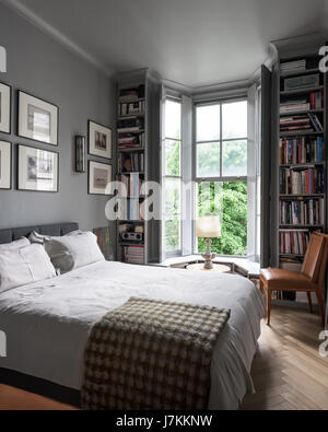 Calm grey tones and book shelving in bedroom with 1940s Murano glass wall lights - Stock Photo