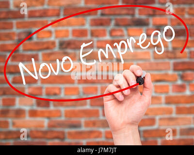 Man Hand writing  Novo Emprego (New Job in Portuguese)   with black marker on visual screen. Isolated on bricks. - Stock Photo
