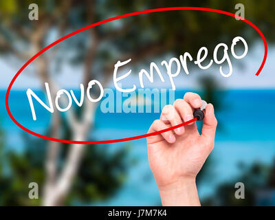 Man Hand writing  Novo Emprego (New Job in Portuguese)   with black marker on visual screen. Isolated on nature. - Stock Photo