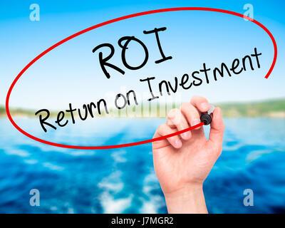 Man Hand writing ROI  Return on Investment with black marker on visual screen. Isolated on nature. Business, technology, - Stock Photo