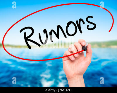 Man Hand writing Rumors  with black marker on visual screen. Isolated on background. Business, technology, internet - Stock Photo