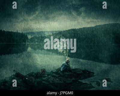 Young boy, artist with a guitar and books, sit down on a rocky shore near the lake and forest. Bad mood, hard thinking, - Stock Photo