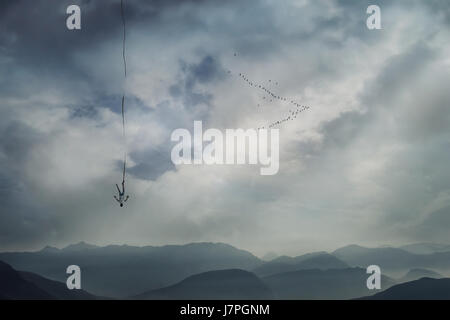 Young man falling from the sky with a rope tied to his leg as safety insurance. Base jump, mysterious crash, life - Stock Photo