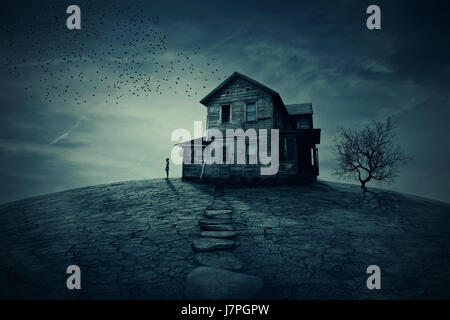 Young man stand at the corner of a ravaged house, looking far away for someone. A ghost, desolated house with a - Stock Photo