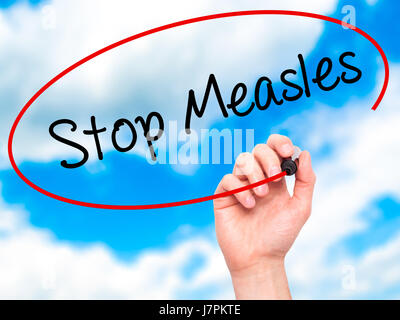Man Hand writing Stop Measles  with black marker on visual screen. Isolated on background. Business, technology, - Stock Photo