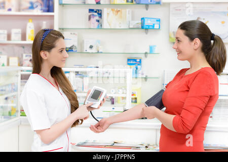 Pharmacist showing a digital blood pressure measurement device to a customer - Stock Photo