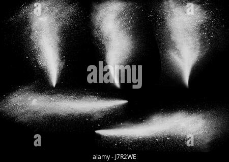 Freeze motion of white powder paint exploding streaming up isolated on black dark background. Abstract design of - Stock Photo