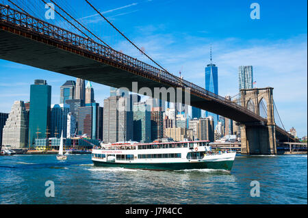 Bright scenic morning view of the Brooklyn Bridge and Lower Manhattan skyline as viewed from the shore of the DUMBO - Stock Photo