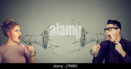 Quarrel between woman and man screaming at each other in megaphone - Stock Photo