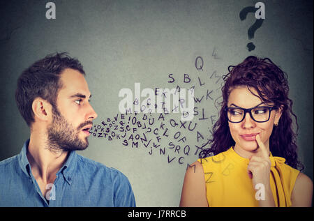 Language barrier concept. Handsome man talking to an attractive young woman with question mark - Stock Photo
