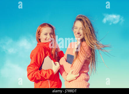 Two young attractive girls having fun outdoors enjoying fresh air on windy summer day - Stock Photo